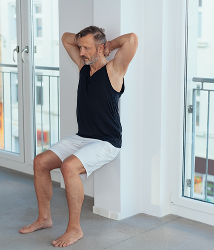 man exercising wall sit during indoor workout for legs muscles